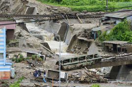 Damaged cars and buildings are seen after a landslide caused by heavy rains due to Typhoon Neoguri in Nagiso town, Nagano prefecture, in this photo taken by Kyodo, July 10, 2014.