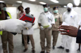 A Nigerian health official uses a thermometer on a worker at the arrivals hall of Murtala Muhammed International Airport in Lagos, Nigeria, Monday, Aug. 4, 2014. Nigerian authorities on Monday confirmed a second case of Ebola in Africa's most populou...