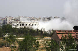 Smoke rises from a part of the Mleha town in the suburb of Damascus during the clashes between rebel fighters and forces loyal to Syria's President Bashar al-Assad, April 12, 2014.