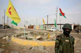 FILE - A soldier of the Kurdish Democratic Party (KDP) patrols at a destroyed roundabout in the town of Snuny, close to Sinjar, northern Iraq, Jan. 29, 2015.