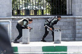Members of Iranian forces take cover during an attack on the Iranian parliament in central Tehran, Iran, June 7, 2017.