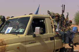Members of an armed group sit in a vehicle in Kidal, Mali, July 13, 2016. Clashes have been reported in the restive northern city between pro-government and former rebel groups, both based there since February.