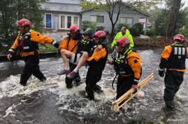 Search and Rescue workers from New York rescue a man from flooding caused by Hurricane Florence in River Bend, North Carolina, U.S. in this Sept. 14, 2018 handout photo.