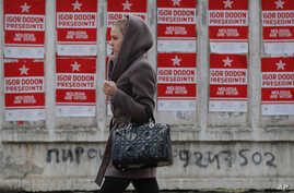 A girl walks by campaign posters for socialist presidential candidate Igor Dodon, in Chisinau, Moldova, Nov. 12, 2016.