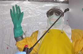 A health worker is sprayed with disinfectant after he worked with patients that contracted the Ebola virus, at a clinic  in Monrovia, Liberia, Monday, Sept. 8, 2014.  Border closures, flight bans and mass quarantines are creating a sense of siege in