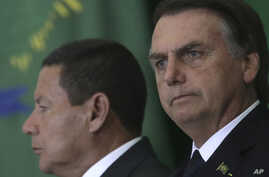 While Brazil's President Jair Bolsonaro was attending the World Economic Forum,  Jan. 23, 2019, Vice President Hamilton Mourao, left, signed the decree expanding exceptions within the 2011 transparency law.