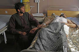 An Afghan wounded man, right, lies on the bed in a hospital as his relative sits on a chair beside him in the city of Kandahar, south of Kabul, Afghanistan, July 9, 2014.