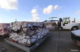 Workers load humanitarian aid from United Nations onto a plane for Syrian families, in Arbil airport, about 220 miles north of Baghdad, Dec. 15, 2013.