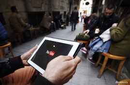 A man tries to get connected to YouTube with his tablet at a cafe in Istanbul, March 27, 2014.