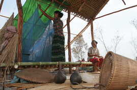 A Cambodian woman hangs her mosquito net in the temporary dwelling in the fields that she and her husband are clearing to farm.