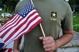 A Pakistani recruit, 22, who was recently discharged from the U.S. Army, holds an American flag as he poses for a picture, July 3, 2018. The man asked his name and location to be undisclosed for safety reasons. The AP interviewed three recruits from