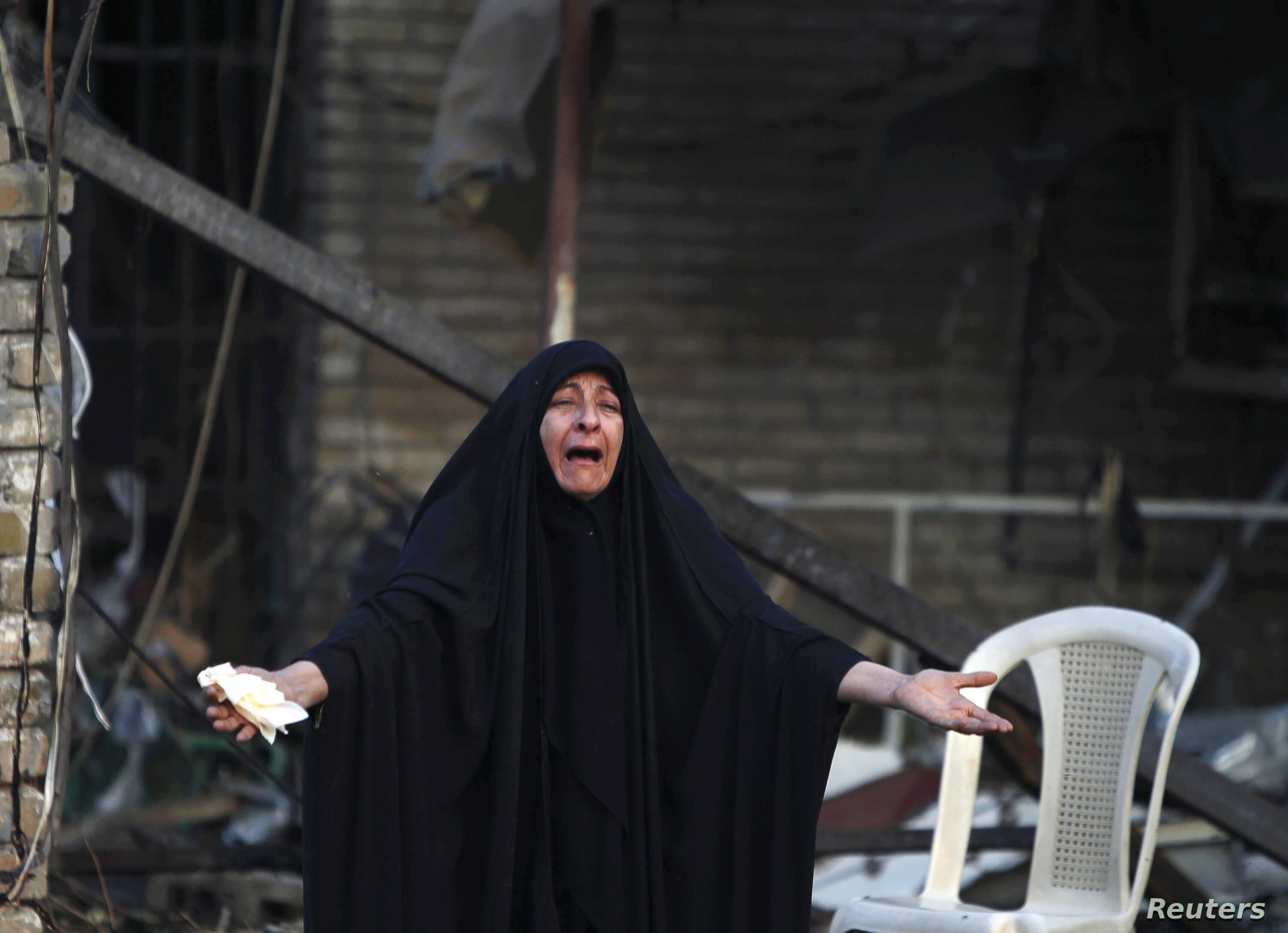 A woman reacts at the site of a car bomb attack that killed a parliament member and 24 others Tuesday, at the entrance to the Shi'ite neighborhood of Kadhimiya in Baghdad, Oct. 15, 2014.