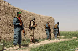 Afghan policemen keep watch during a battle with the Taliban in Nahr-e Saraj district of Helmand province, Afghanistan, May 11, 2016.