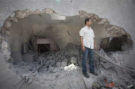 In this photo made on a government organized tour, a man stands next to a hole in a wall at the Gadhafi family compound in a residential area of Tripoli, Libya, Sunday, May 1, 2011. Libyan leader Moammar Gadhafi escaped a NATO missile strike in Tripo