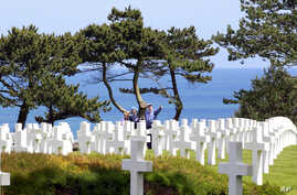 Visitors walk among graves at the Colleville American military cemetery, in Colleville-sur-Mer, western France, on  the 71th anniversary of the D-Day landing, June 6, 2015.