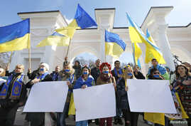 Women with their mouths taped over and others participants attend a pro-Ukraine rally in Simferopol, March 13, 2014.