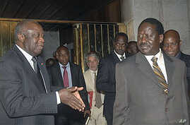 Ivory Coast strongman Laurent Gbagbo, left, talks with Kenyan Prime Minister Raila Odinga, an African Union envoy sent to mediate the ongoing Ivorian political standoff, following a meeting at the presidential palace in Abidjan, Ivory Coast, Jan 17,