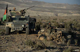 FILE - In this photograph taken on December 3, 2016, Afghan security forces take positions following an operation against Islamic State (IS) militants in Pachir Wa Agam district of Nangarhar province.