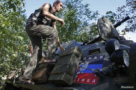 A pro-Russian separatist climbs atop an armored personnel carrier as he guards a position in the eastern Ukrainian town of Ilovaysk Aug. 31, 2014.