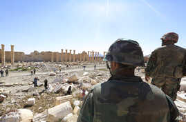 In this picture taken Friday, April 1, 2016, soldiers look over damage at the historical Bel Temple in the ancient city of Palmyra in the central city of Homs, Syria.