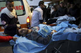 Palestinian medics a wounded youth, who was shot by Israeli troops during a protest at the Gaza Strip's border with Israel, into the treatment room of Shifa hospital in Gaza City, Friday, Jan. 11, 2019.