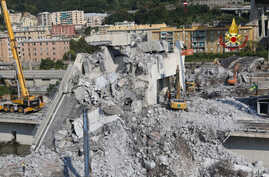 Firefighters remove rubble of the collapsed Morandi highway bridge, in Genoa, Italy, Aug. 18, 2018.