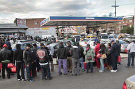 Gas customers on foot with portable containers and lines of vehicles wait for gas pumps to open at a service station Saturday, Nov. 3, 2012 in the Brooklyn borough of New York.