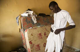 Abdulkadir Abdullahi arranges his school uniform in Maiduguri, Nigeria, October 2016. (C. Oduah/VOA)