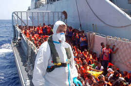 FILE - Migrants wait to be boarded on the San Giusto Navy ship, along the Mediterranean sea, off the Sicilian island of Lampedusa,, Aug. 23, 2014.