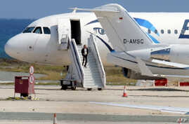 A man believed to be the hijacker of the EgyptAir Airbus A-320, which was diverted to Cyprus, leaves the plane before surrendering to security forces after a six-hour standoff on the tarmac at Larnaca airport's largely disused old terminal on March 2