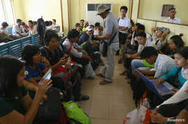 FILE - Non-governmental Organizations (NGOs) and International Non-governmental Organizations (INGOs) staff wait at Sittwe Airport to return to Rangoon, in Sittwe, March 28, 2014.