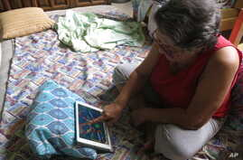 n this April, 5, 2017 photo, Mirna Lugo plays a game on her tablet to pass the time after dragging her mattress into the coolest part of her house because Puerto Rico's public power company cut the power in her neighborhood.