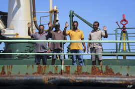 FILE - Crew members wave from aboard the Aris 13 oil tanker, which was released by pirates after negotiations by officials and local elders in Somalia's semiautonomous northeastern state of Puntland, March 19, 2017.