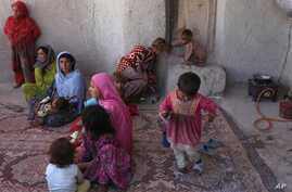 In this Monday, May 30, 2016 photo, Afghan internally displaced family are seen at their temporary home in a camp for internally displaced people in Kabul, Afghanistan.