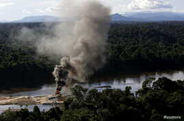 An illegal gold dredge is seen burning down at the banks of Uraricoera River during Brazil's environmental agency operation against illegal gold mining on indigenous land, in the heart of the Amazon rainforest, in Roraima state, Brazil, April 15, 201
