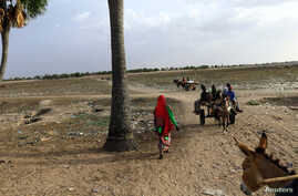 FILE - People walk toward the border with Central African Republic in Um Dafuq, Sudan, May 29, 2017.
