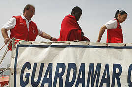 A would-be immigrant arrives with members of the Red Cross after being rescued from the sea at the port of Motril, Spain, May 6, 2011.
