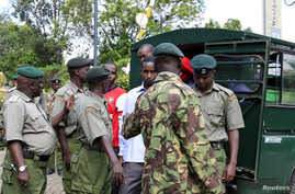 FILE - Four men charged with helping al Qaida-linked militants launch an attack on the Westgate mall, arrive under guard from prison warders during a court session in Nairobi.