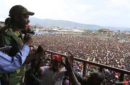 The M23 rebels spokesman Vianney Kazarama (L) speaks to the crowd gathered at a stadium in Goma, Democratic Republic of Congo, November 21, 2012.