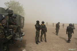 FILE - Cameroonian soldiers stand guard amidst dust kicked up by a helicopter in Kolofata, Cameroon, March 16, 2016. Part of a multinational force, the soldiers have intensified their fight against Boko Haram militants.