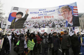 A banner showing pictures of impeached South Korean President Park Geun-hye and U.S. President Donald Trump is displayed as supporters of Park wave flags of the United States and South Korea during a rally opposing her impeachment in Seoul, South Ko