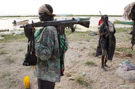 A Turkana man holds a rifle on the western shore of Lake Turkana, close to Todonyang in northern Kenya, Sept. 25, 2014. The Turkana people have historically clashed over ethnic differences and precious resources.