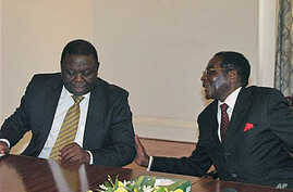 Zimbabwean President Robert Mugabe, right, chats to Prime Minister Morgan Tsavangirai during their end of year press conference at State House in Harare, saying they were dispelling rumors of disunity in the Government of National Unity, December 20,