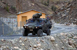 FILE - A Turkish military armoured personnel carrier drives past a small patrol base high in the mountains of Cukurca near the Iraqi border in southeastern Turkey.