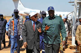 FILE - South Sudan's Oil minister Ezekiel Lul Gatkuoth (R) and Sudan's oil minister, Azhari Abdel Qader arrive for a ceremony marking the restarting of crude oil pumping at the Unity oil fields in South Sudan, Jan. 21, 2019.