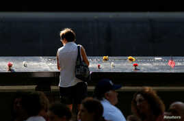 Guests looks at the memorial during the ceremony marking the 15th anniversary of the attacks on the World Trade Center at The National September 11 Memorial and Museum in Lower Manhattan in New York City, Sept. 11, 2016.