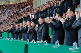 North Korean leader Kim Jong Un gestures during a men's football match between Sonbong and Hwoebul teams for the Mangyongdae Prize Sports Games at Kim Il Sung Stadium on Monday, in this undated photo released by North Korea's Korean Central News Agen