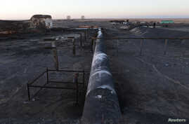 FILE - Damaged tanks and pipelines are seen at the oil port of Ras Lanuf, Libya January 11, 2017.