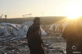Residents and Free Syrian Army fighters are seen near damaged tents for Syrian refugees after shelling by forces loyal to Syria's President Bashar al-Assad on the outskirts of Idlib, near the Syrian-Turkey border, November 26, 2012.