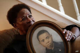 In this Aug. 9, 2018 photo, Eberlene King poses with a photograph of her brother William Roy Prather when he was about 15-years-old at her home in Doraville, Georgia.